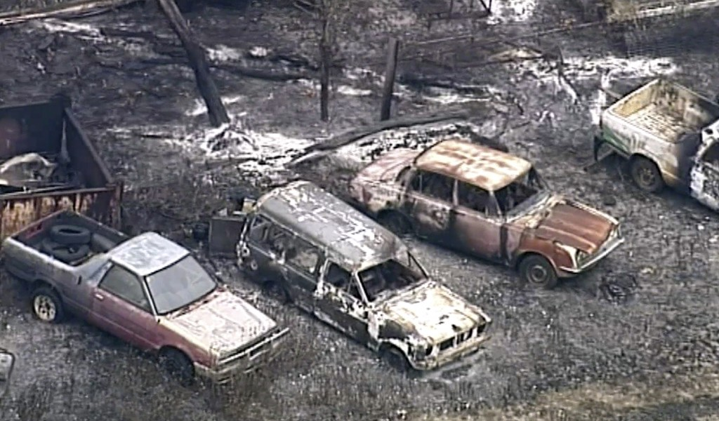 In this image made from aerial video taken Tuesday, Nov. 27, 2018, burned out vehicles are seen on a scorched landscape in the Deepwater area of Queen