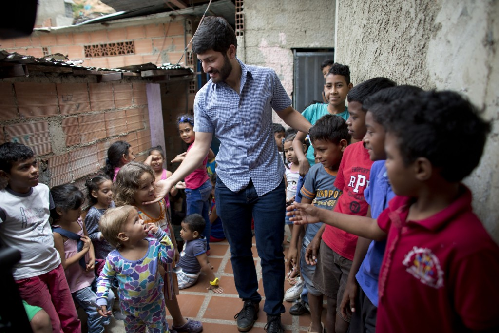 In this Aug. 26, 2018 photo, Roberto Patino greets children at a children's center in the La Vega neighborhood of Caracas, Venezuela. Patino, a rising