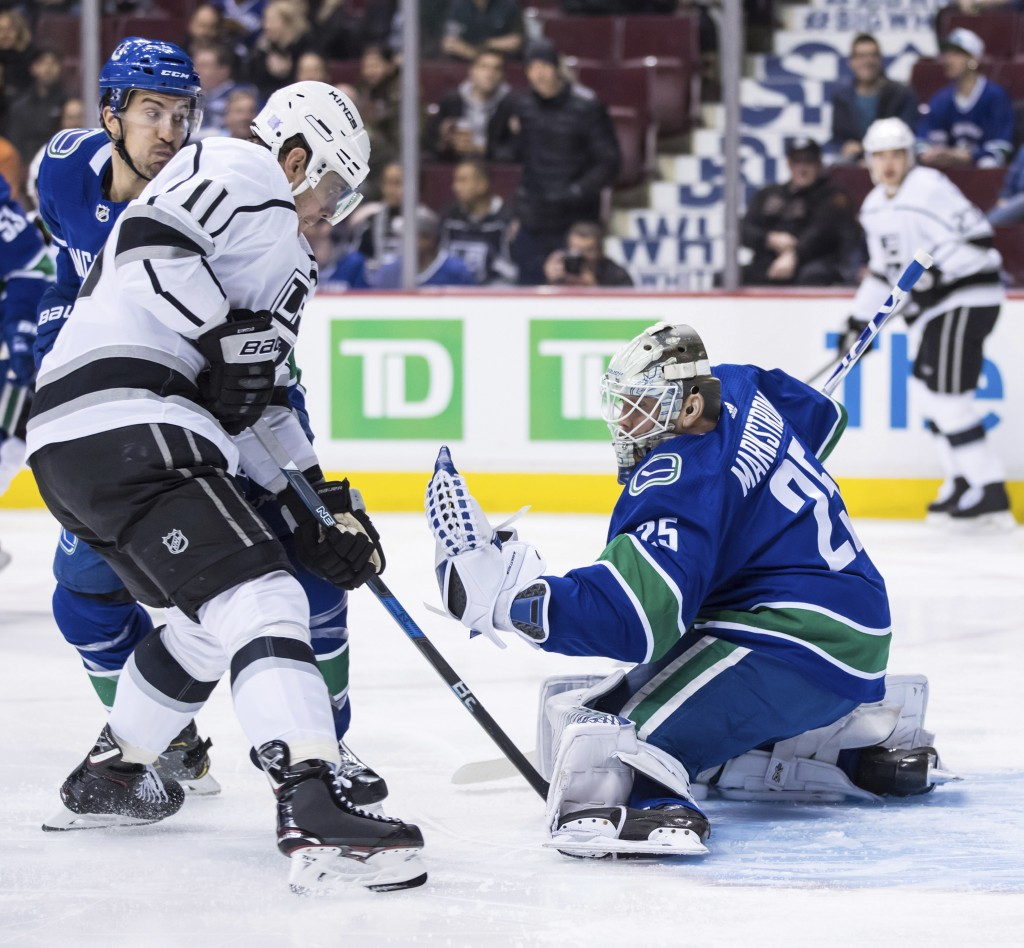Los Angeles Kings' Anze Kopitar (11), of Slovenia, watches as Vancouver Canucks goalie Jacob Markstrom (25), of Sweden, makes a glove save during the ...