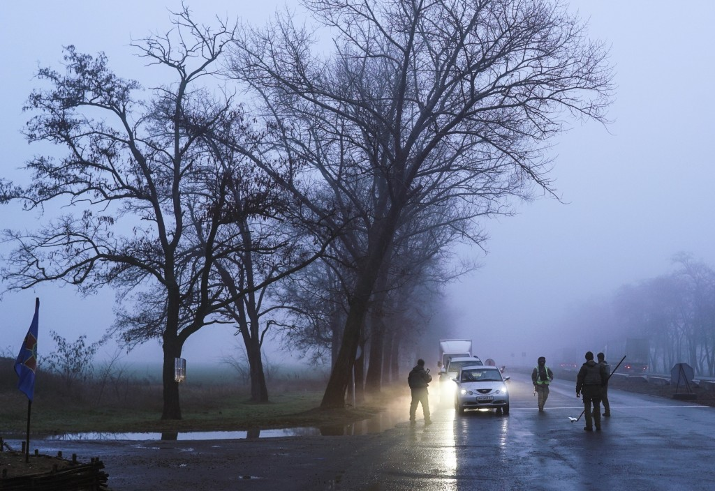 Ukrainian national guard soldiers and a police officer stop a car to check documents at the checkpoint near the city of Mariupol, south coast of Azov ...