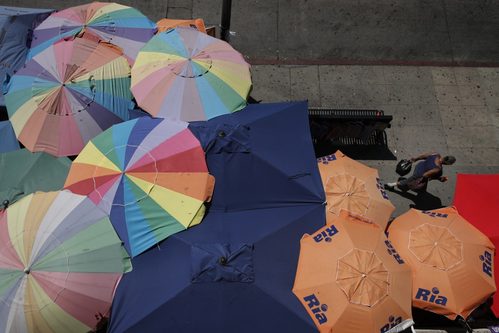 In this Aug. 1, 2018 photo, a woman walks on a sidewalk covered with street vendors' sun-faded umbrellas in Los Angeles. They seem to be everywhere on
