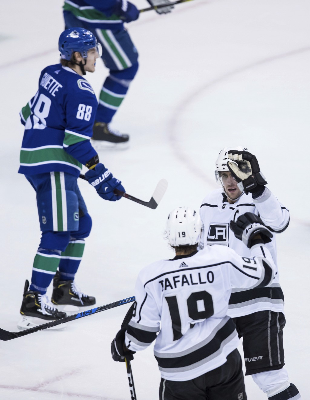 Los Angeles Kings' Anze Kopitar, front right, of Slovenia, and Alex Iafallo (19) celebrate Iafallo's goal as Vancouver Canucks' Adam Gaudette (88) ska...