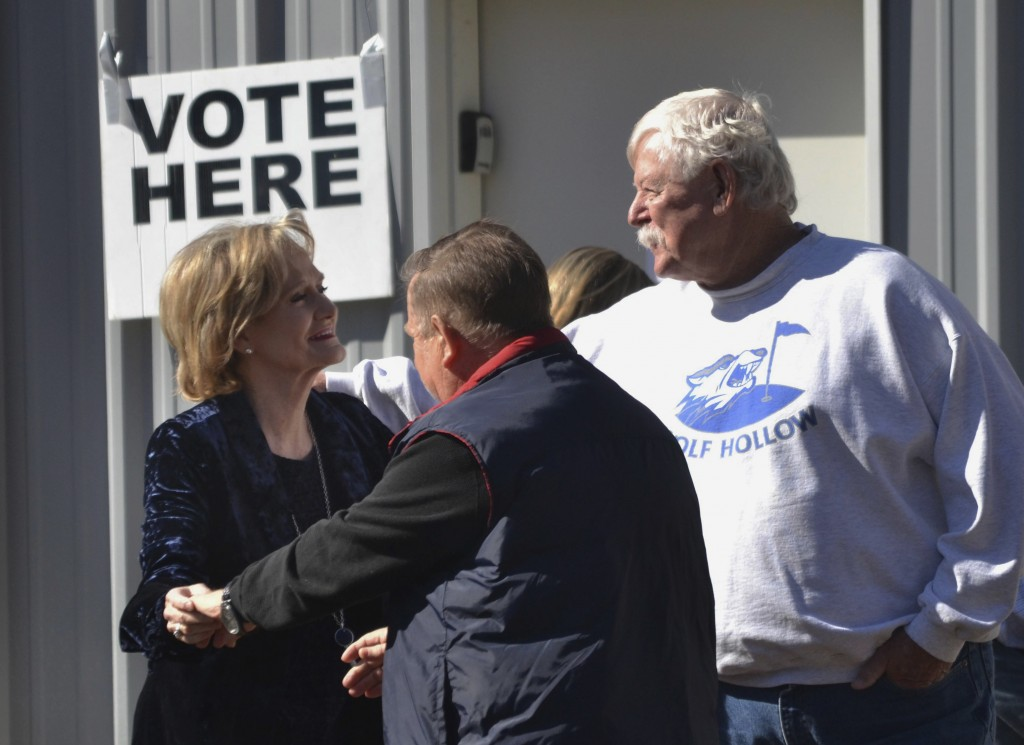 Appointed Republican U.S. Sen. Cindy Hyde-Smith, center, greets neighbors at her Brookhaven, Miss., precinct after voting Tuesday, Nov. 27, 2018, in h...