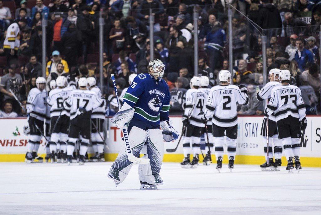 Vancouver Canucks goalie Jacob Markstrom, front, of Sweden, skates to the bench as the Los Angeles Kings celebrate Dustin Brown's overtime goal during