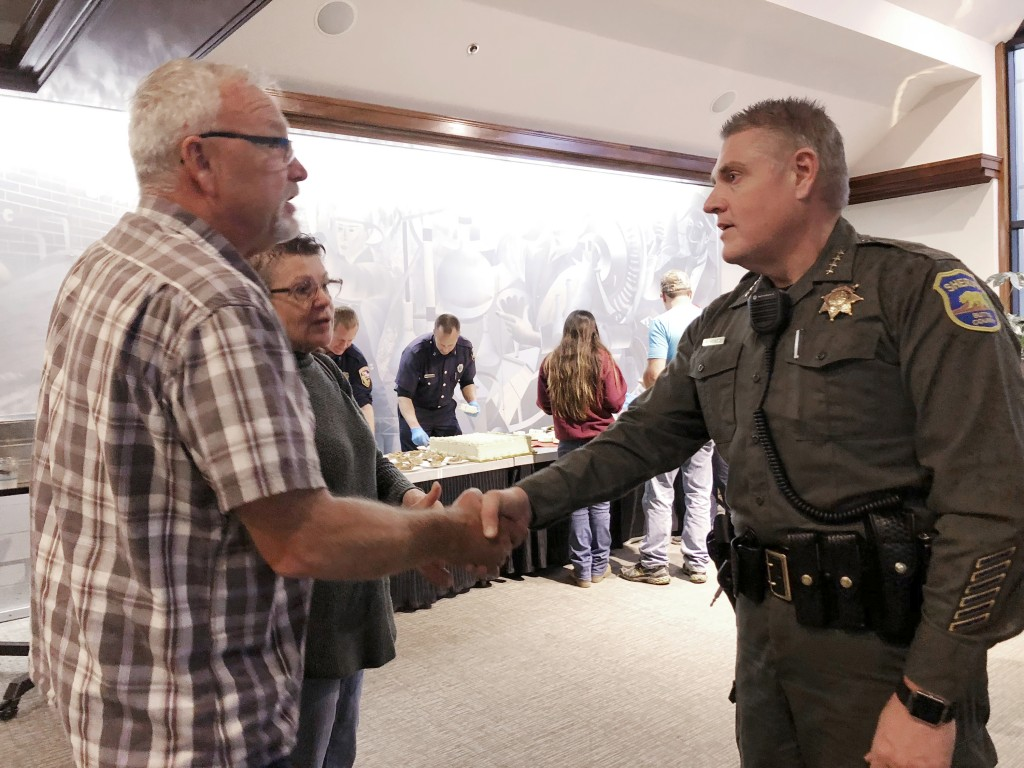 In this Nov. 22, 2018 photo, Butte County Sheriff Kory Honea greets Roy and Linda Strop at a community Thanksgiving dinner at Sierra Nevada Brewing Co