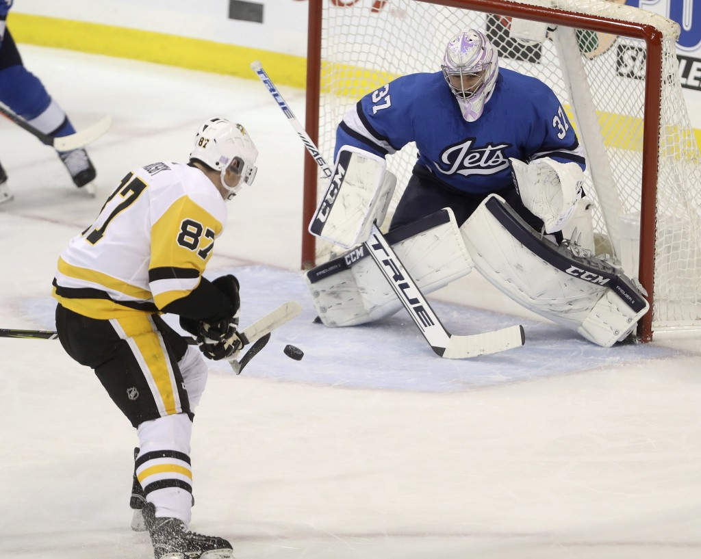 Pittsburgh Penguins' Sidney Crosby (87) scores on Winnipeg Jets' goaltender Connor Hellebuyck (37) during the first period of an NHL hockey game, Tues...