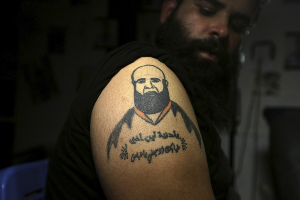 In this Tuesday. Oct. 23, 2018, photo, Zuhair Atwan displays tattoo of his brother, who was killed in sectarian violence, in a tattoo studio in Baghda
