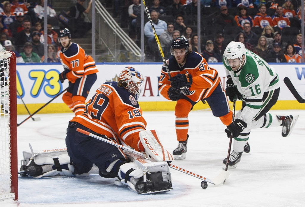 Dallas Stars' Jason Dickinson (16) is stopped by Edmonton Oilers goalie Mikko Koskinen (19) as Connor McDavid (97) looks to clear the puck during firs
