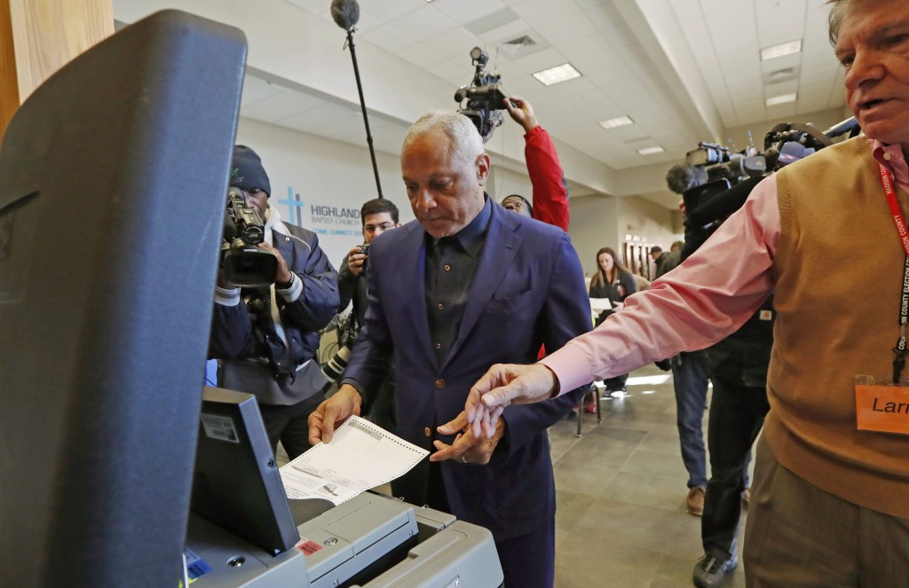 Democrat Mike Espy, left feeds his ballot into the submission machine, as directed by poll manager Larry Greer, Tuesday, Nov. 27, 2018 in Ridgeland, M...
