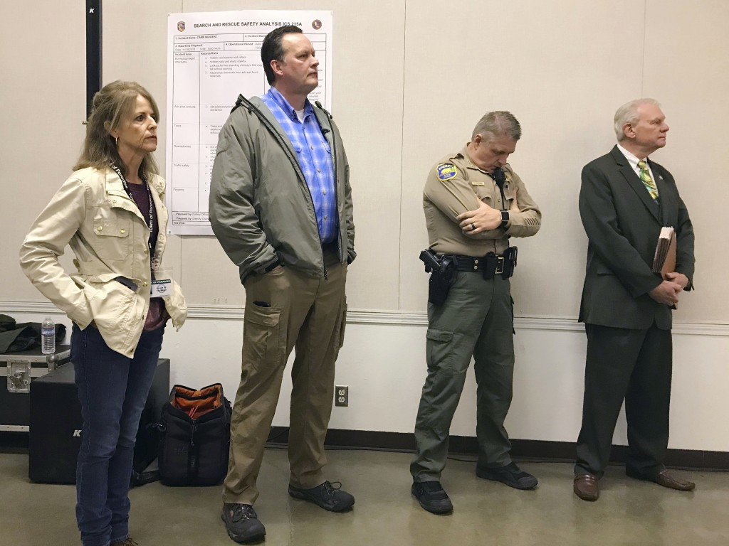In this Nov. 21, 2018 photo, Butte County Sheriff Kory Honea, second from right, bows his head while other officials give updates about a massive Nort...