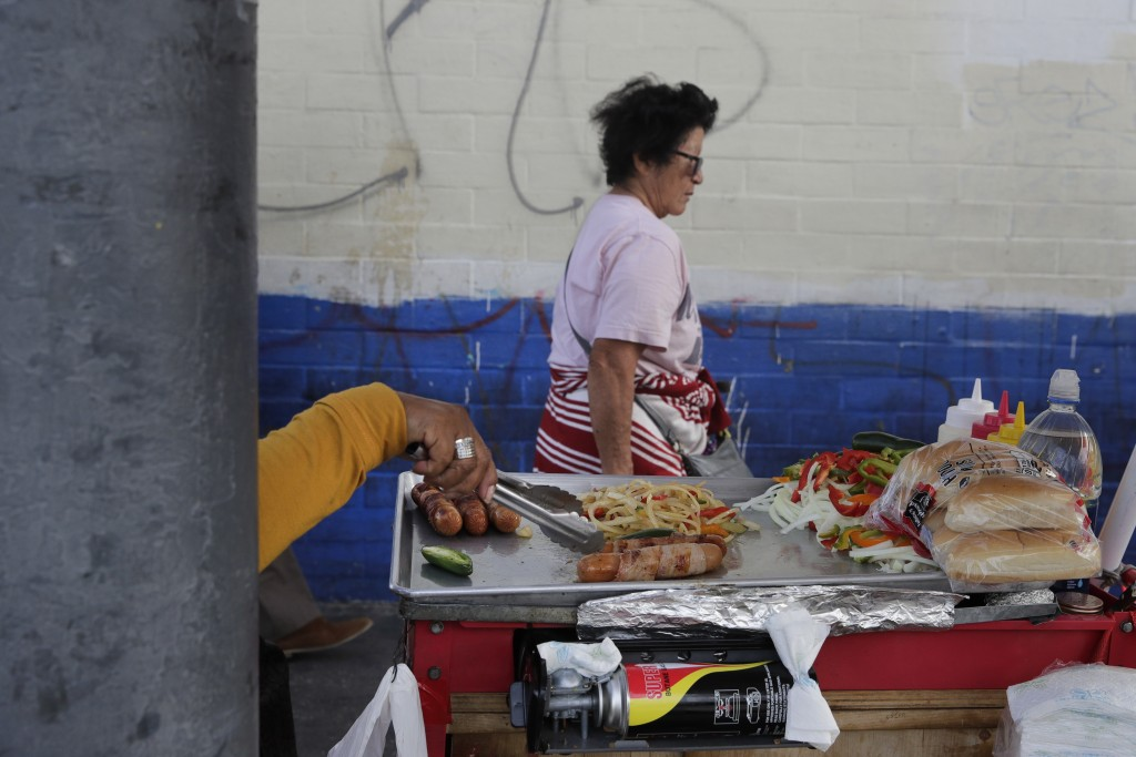 A food vendor prepares hot dogs on a sidewalk Tuesday, Nov. 27, 2018, in Los Angeles. They seem to be everywhere on the streets of Los Angeles - pushc...
