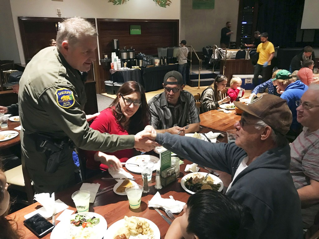 FILE - In this Nov. 22, 2018, file photo, Butte County Sheriff Kory Honea greets Paradise evacuees at a community Thanksgiving dinner at Sierra Nevada