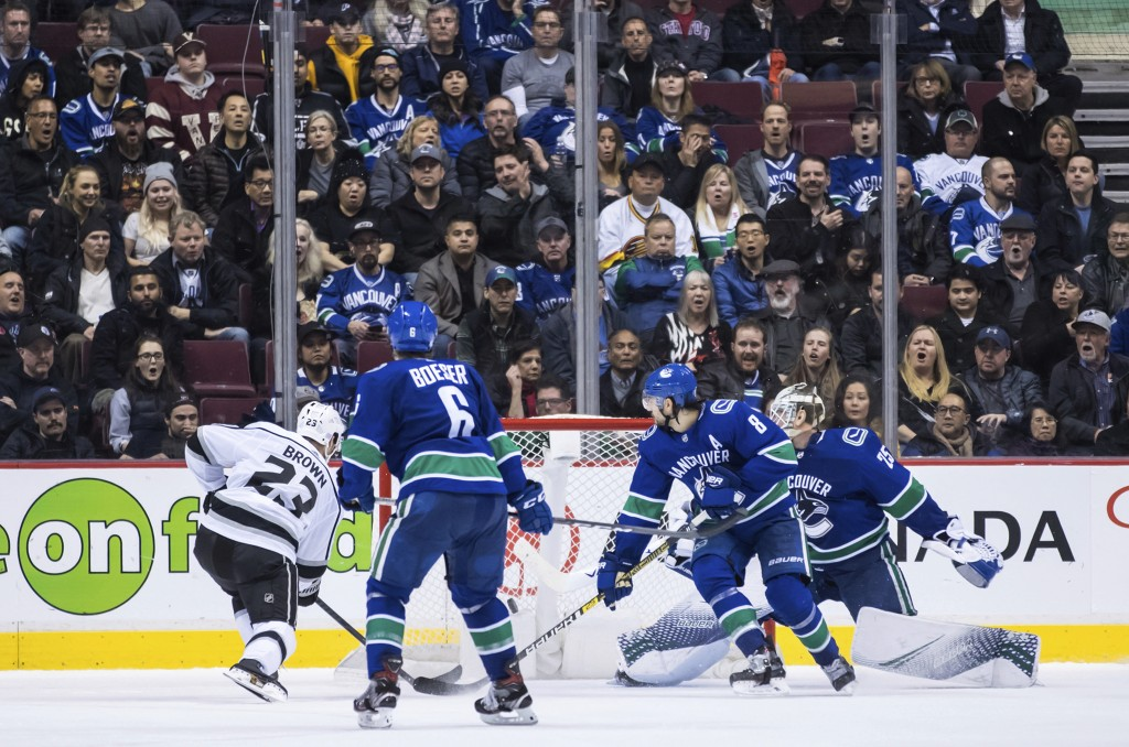 Los Angeles Kings' Dustin Brown (23) scores against Vancouver Canucks goalie Jacob Markstrom, right, of Sweden, as Brock Boeser (6) and Chris Tanev (8...