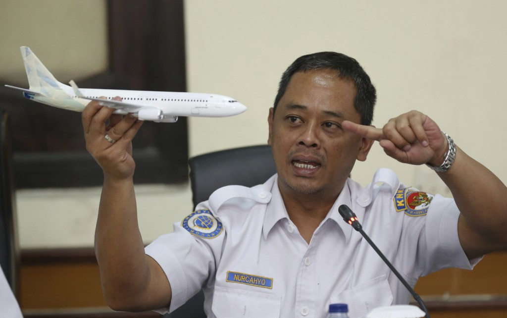 National Transportation Safety Committee investigator Nurcahyo Utomo holds a model of an airplane during a press conference on the committee's prelimi...