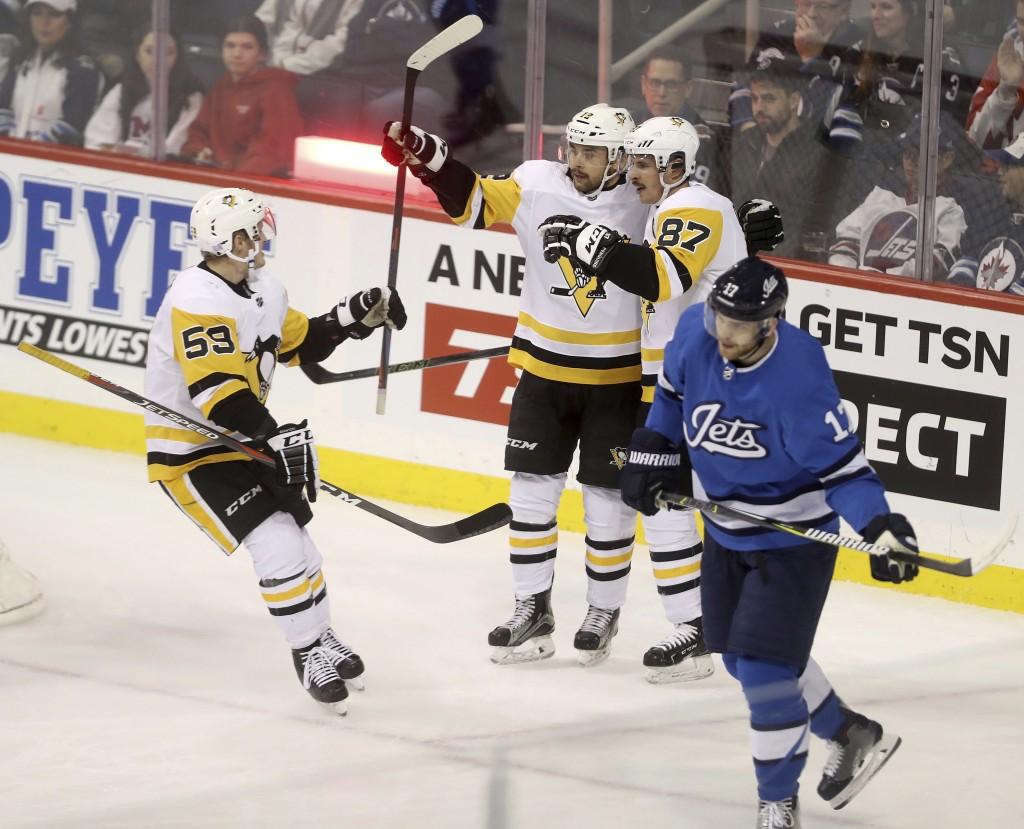 Pittsburgh Penguins' Jake Guentzel (59), Dominik Simon (12) and Sidney Crosby (87) celebrate after Crosby scored as Winnipeg Jets' Adam Lowry (17) ska...