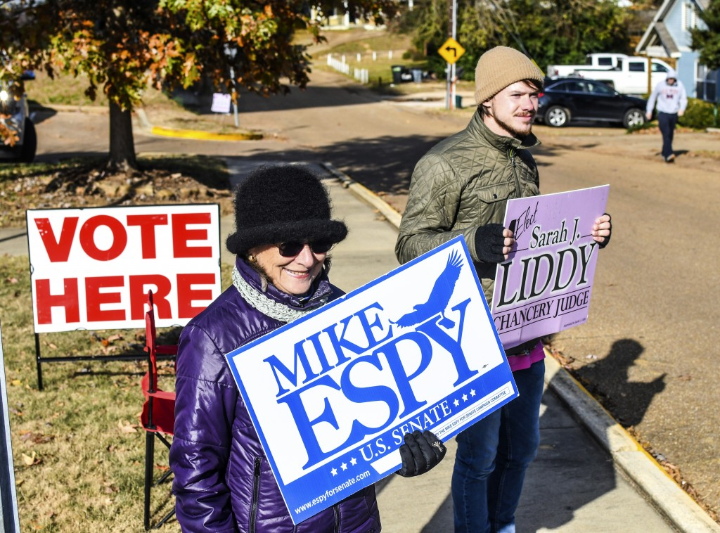 Susan Fino, left, holds a sign for U.S. Senate candidate Mike Espy and Logan Liddy holds one for Susan Liddy, a candidate for judge in the Chancery Co
