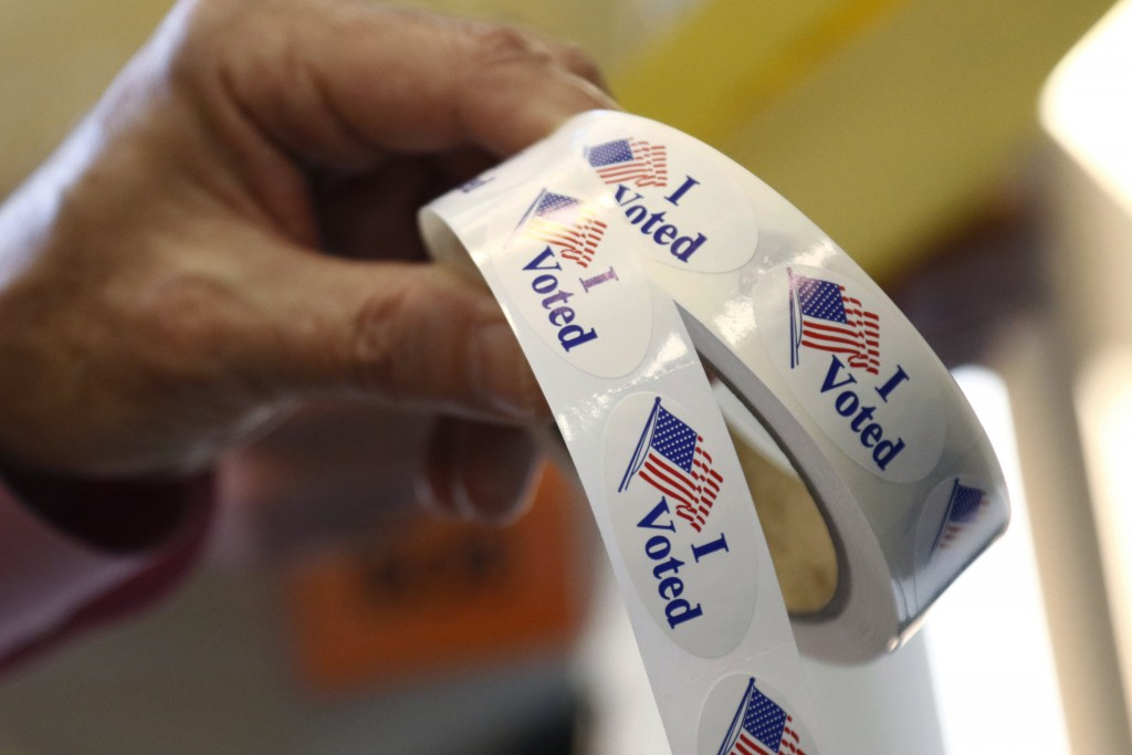 "Poll manager Larry Greer hands holds a roll of ""I Voted"" stickers given each person after voting in a runoff election Tuesday, Nov. 27, 2018 in Ridgel"
