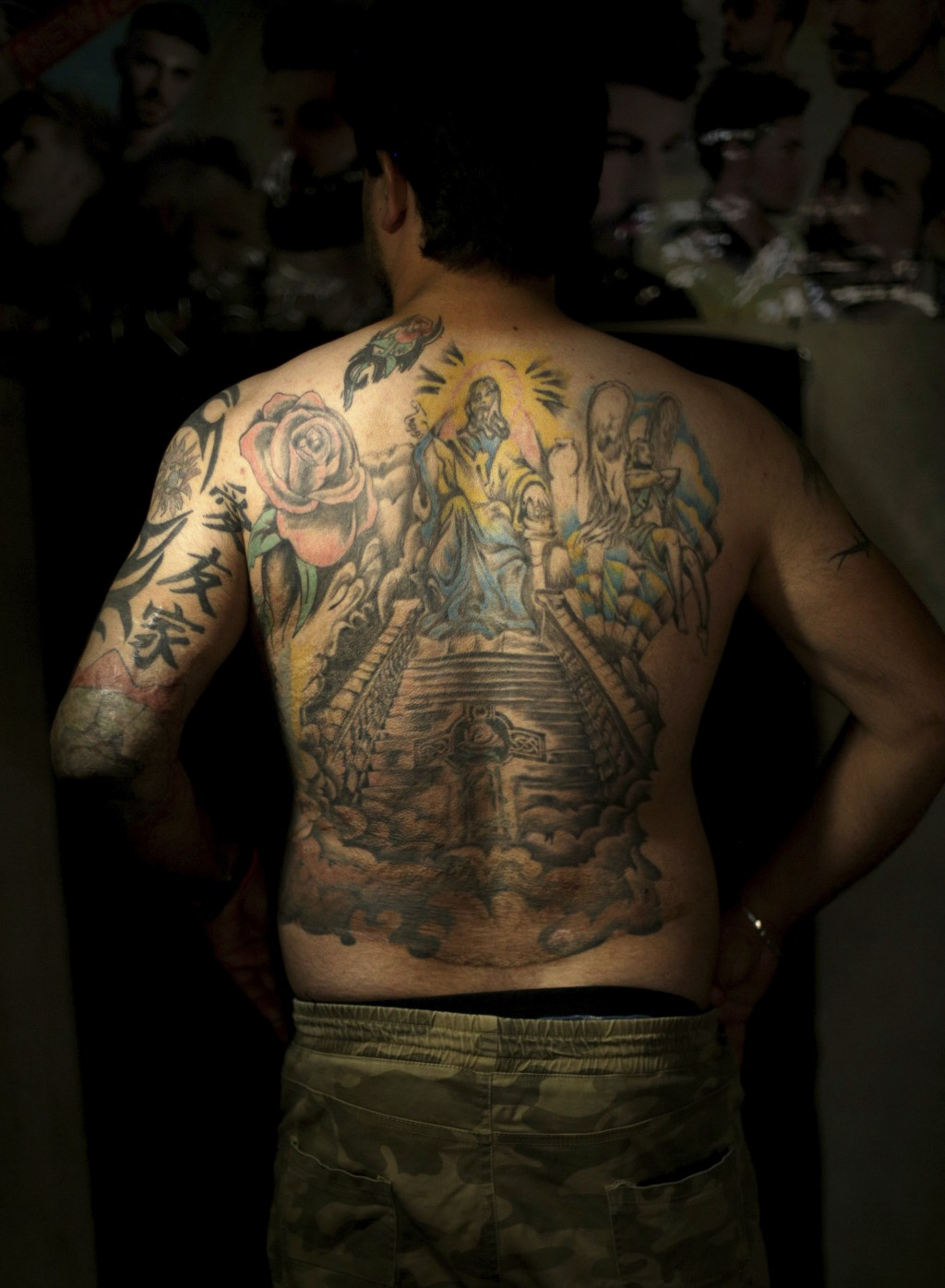 In this Wednesday. Oct. 24, 2018, Iraqi soldier Saad Khudeir displays tattoos on his body to cover scars of the burns he was injured in a car bomb, in