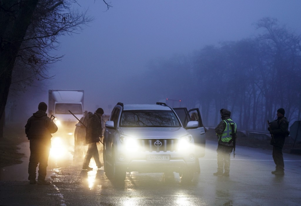 Ukrainian national guard soldiers and a police officer stop a car to check documents at the checkpoint near the city of Mariupol, south coast of Azov