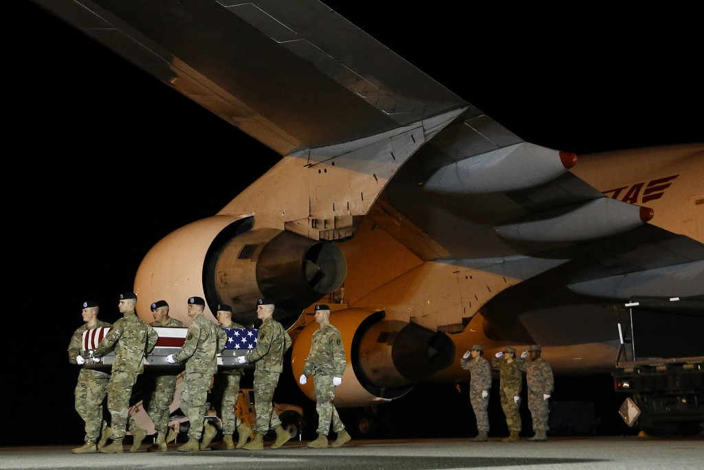 In this Nov. 26, 2018, photo, a U.S. Army carry team moves a transfer case containing the remains of Sgt. Leandro A. Jasso, at Dover Air Force Base, D