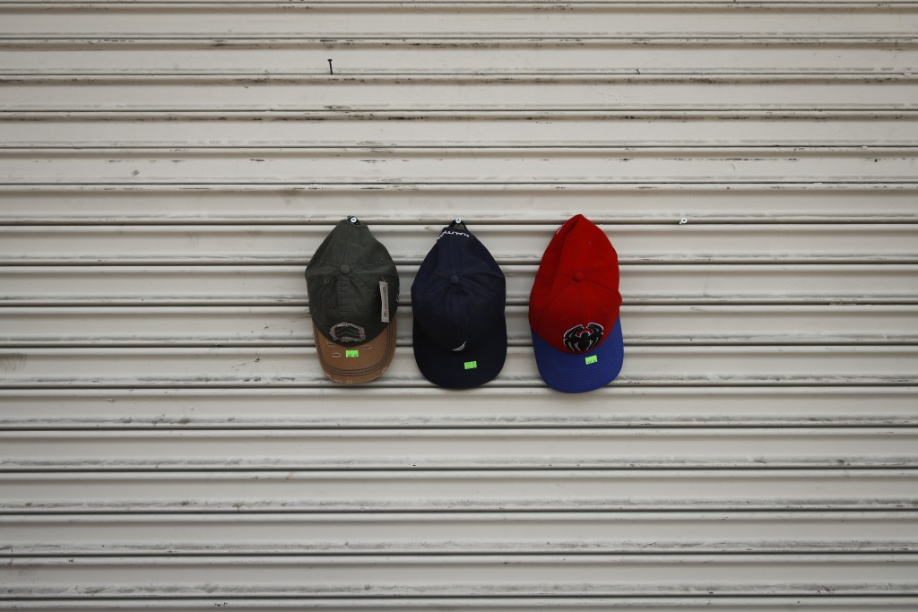 In this Aug. 1, 2018 photo, hats with price stickers hang on the shutters of a closed store in Los Angeles. They seem to be everywhere on the streets