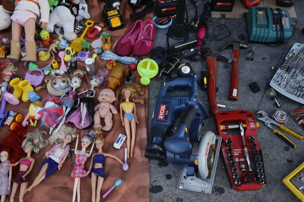 In this Aug. 1, 2018 photo, second hand toys and tools for sale are laid on a sidewalk in Los Angeles. They seem to be everywhere on the streets of Lo...