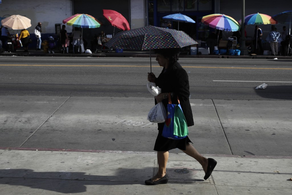 A pedestrian walks with her umbrella as street vendors' umbrellas are lined up along the street Tuesday, Nov. 27, 2018, in Los Angeles. They seem to b...