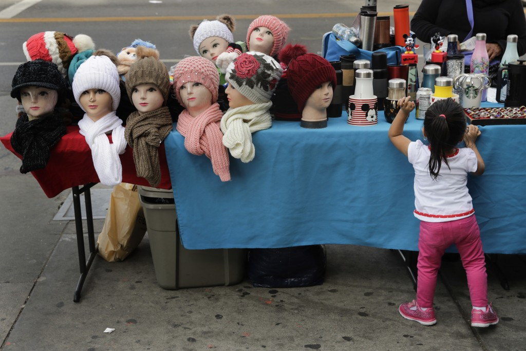 Mannequin heads with beanies are placed on a table as a young girl looks at goods for sale on a sidewalk Tuesday, Nov. 27, 2018, in Los Angeles. They
