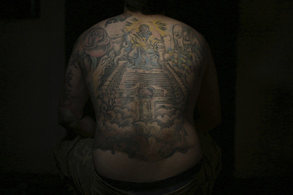 In this Monday. Oct. 22, 2018, Iraqi soldier Saad Khudeir displays his tattoo on his body to cover scars of the burns he suffered from a car bomb, in