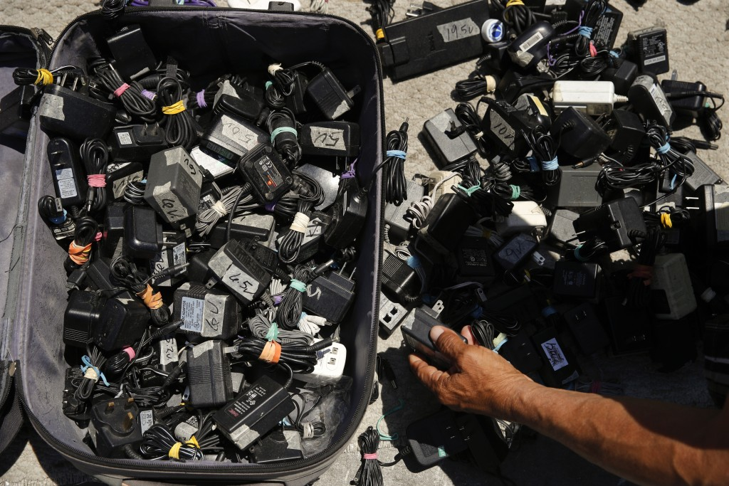 In this Aug. 1, 2018 photo, a man looks for a charger for his phone from a suitcase full of used chargers for sale in Los Angeles. They seem to be eve...