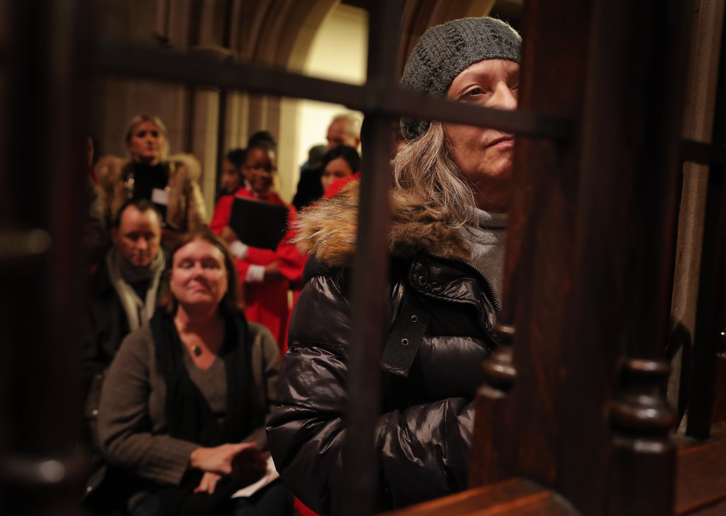 """Spectators watch and listen as the Kroell Family Singers sing """"Silent Night"""" with the Choir of Trinity Wall Street and Trinity Youth Chorus during a c"""