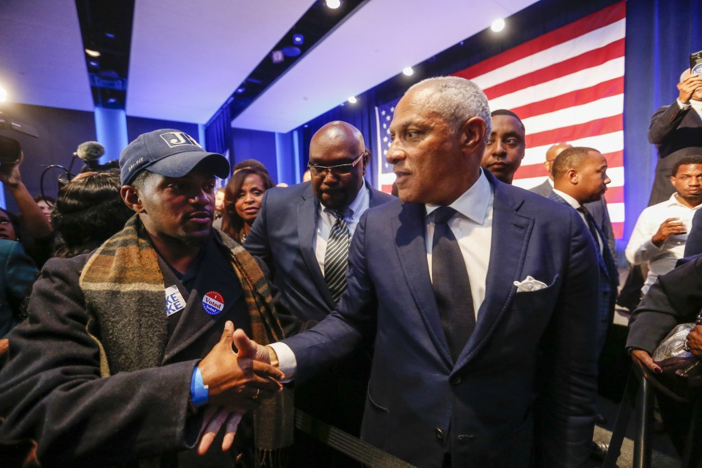 Democrat Mike Espy, right, who sought to unseat appointed U.S. Sen. Cindy Hyde-Smith, R-Miss., shakes hands with a supporter in a crowded auditorium a