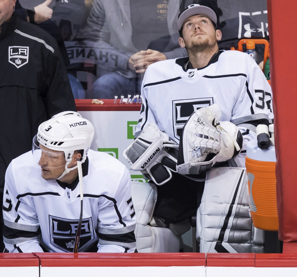 Los Angeles Kings goalie Jonathan Quick, right, sits on the bench beside Dion Phaneuf during the second period of the team's NHL hockey game against t
