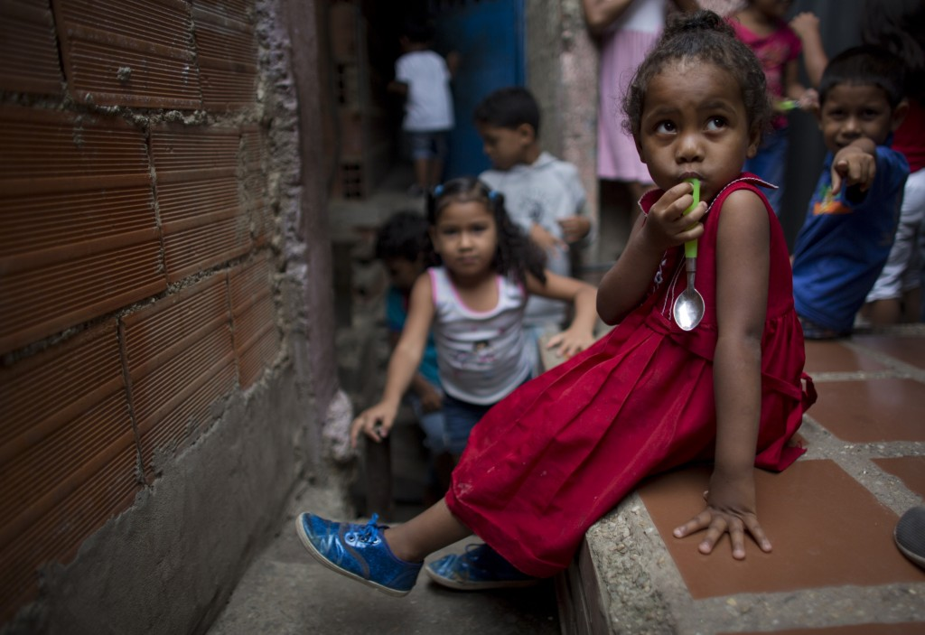 In this Aug. 26, 2018 photo, a girl holds her spoon as she waits to receive a meal at a children's center in the La Vega neighborhood of Caracas, Vene...