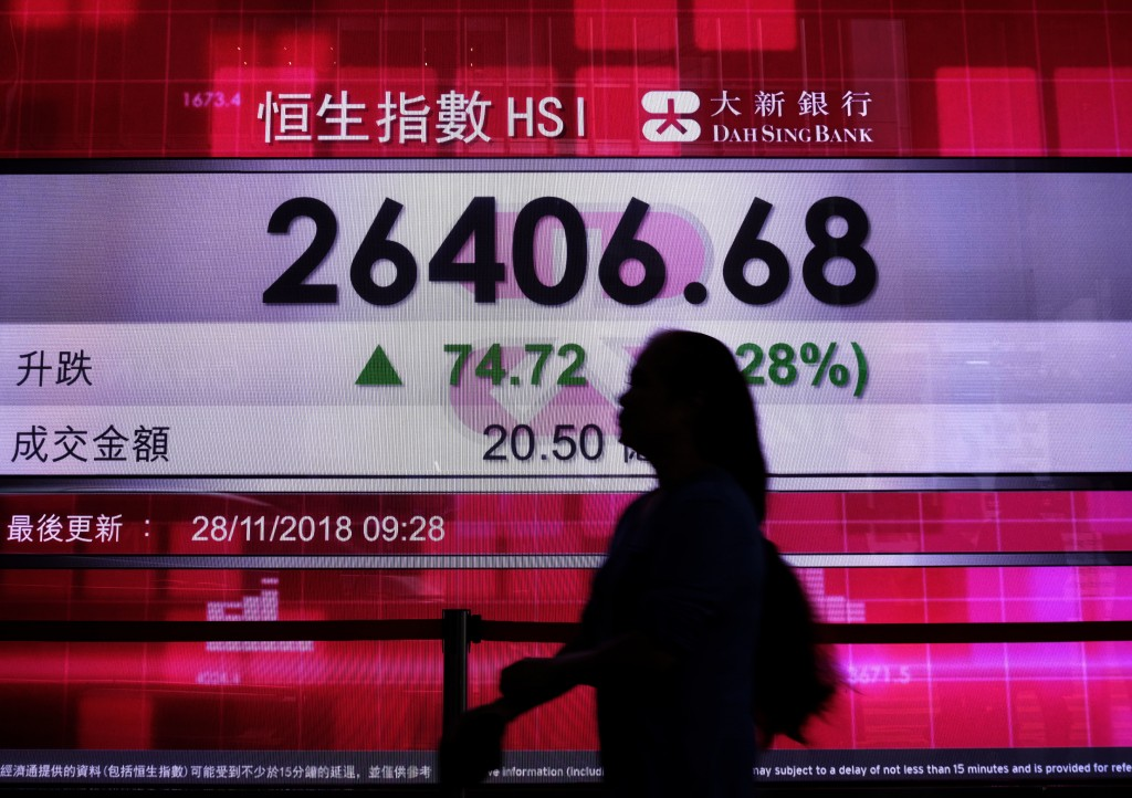 A woman walks past a bank electronic board showing the Hong Kong share index at Hong Kong Stock Exchange Wednesday, Nov 28, 2018. Asian shares were mi...