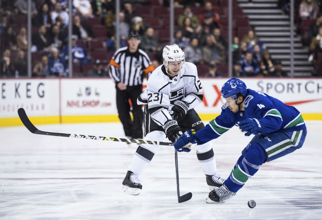 Los Angeles Kings' Dustin Brown (23) passes the puck past Vancouver Canucks' Michael Del Zotto (4) during the first period of an NHL hockey game Tuesd...