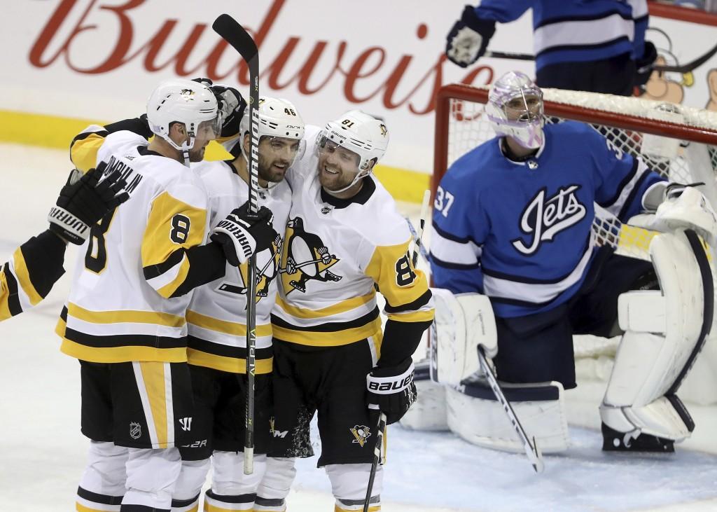 Pittsburgh Penguins' Brian Dumoulin (8), Zach Aston-Reese (46) and Phil Kessel (81) celebrate after Aston-Reese scored against Winnipeg Jets goaltende...