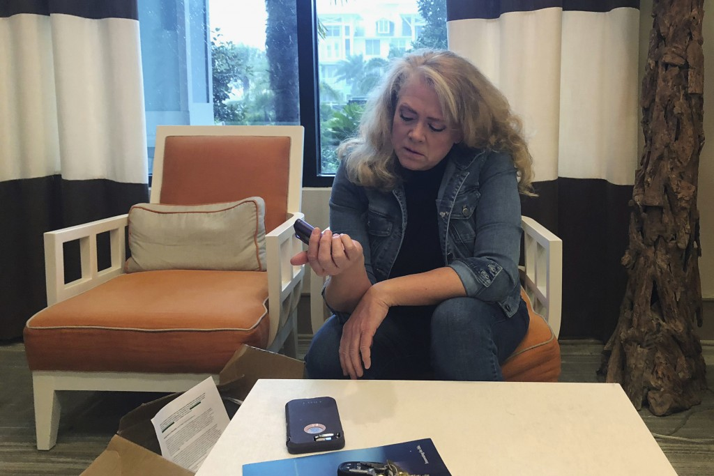 In this Nov. 1, 2018 photo, Polly Varnado looks at her daughter's Medtronic insulin pump in Destin, Fla. Medical device manufacturers and experts say ...