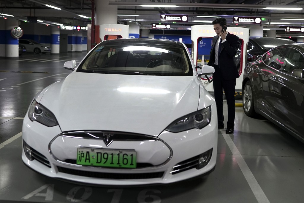 In this Wednesday, Sept. 12, 2018, photo, An Baojia, right, makes a phone call near his Tesla vehicle at a charging station in Shanghai. More than 200...