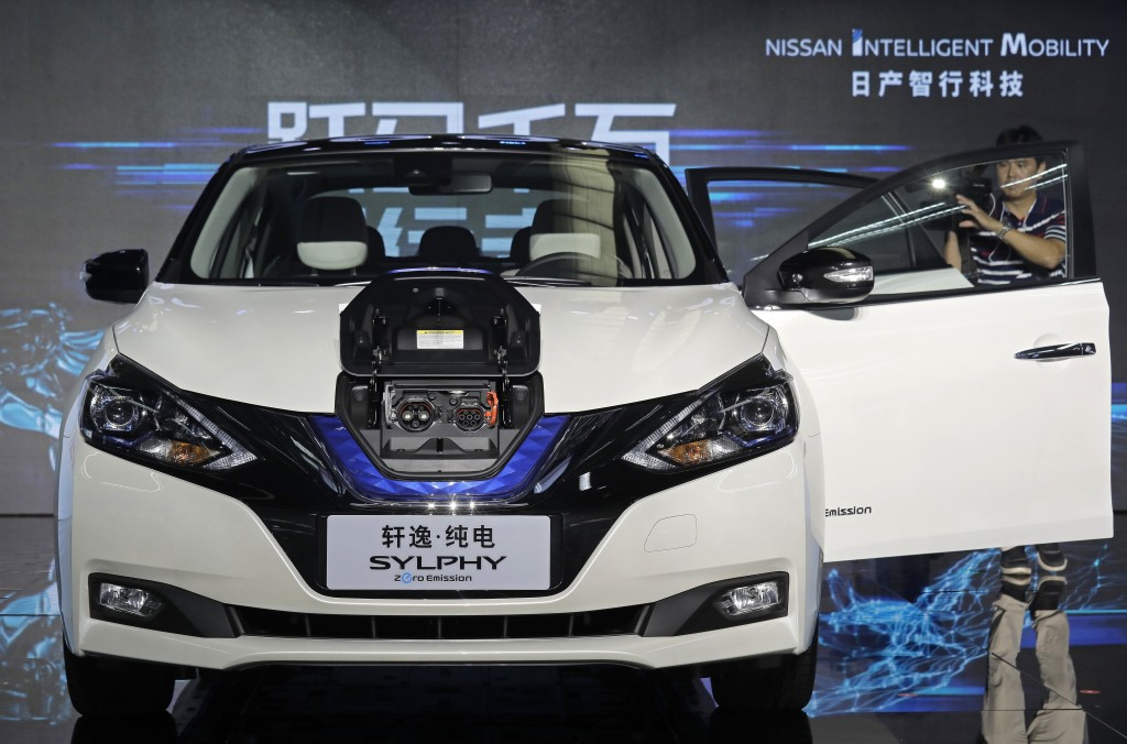 FILE - In this Aug. 27, 2018, file photo, a cameraman takes video of a Nissan Sylphy Zero Emission, the Nissan's first all-electric vehicle built in C...