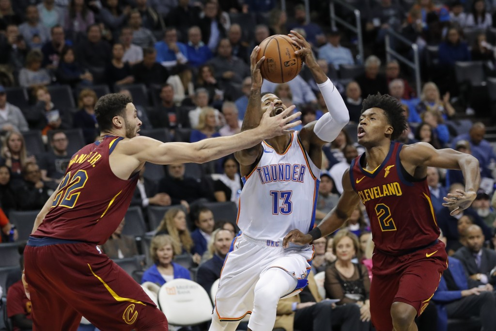 Oklahoma City Thunder forward Paul George (13) drives to the basket between Cleveland Cavaliers forward Larry Nance Jr. (22) and guard Collin Sexton (...
