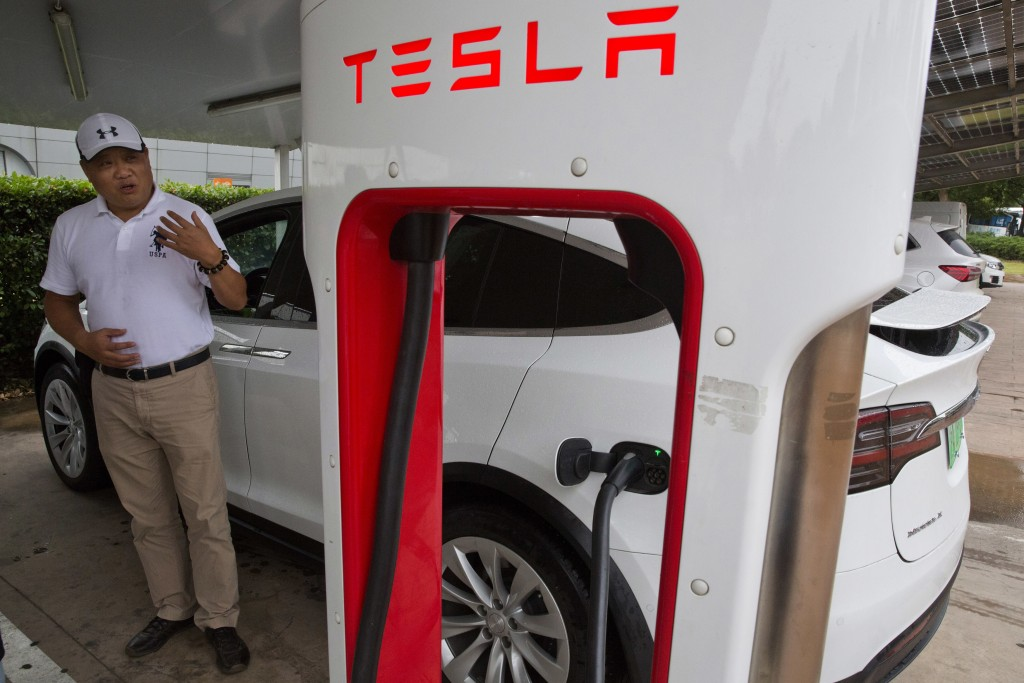 In this June 22, 2018, photo, Shan Junhua chats about privacy near his white Tesla while charging it in Shanghai. When Shan bought his white Tesla Mod...