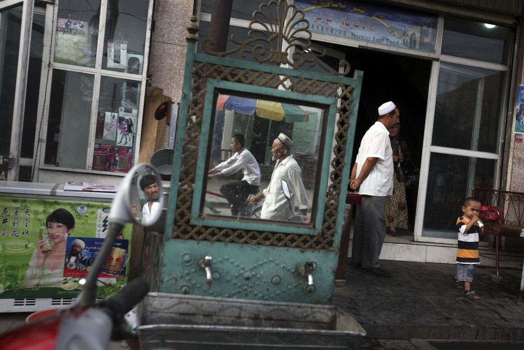 FILE - In this Aug. 6, 2008, file photo, Uighurs are seen outside a restaurant in Kashgar in China's western Xinjiang province. More than a million Ch