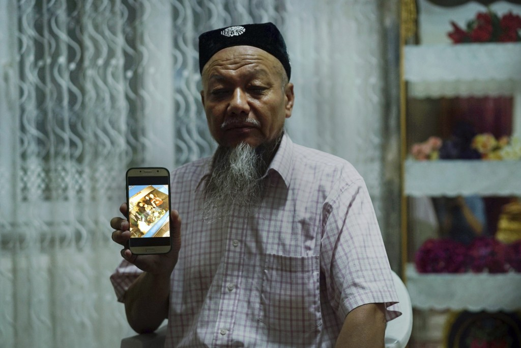 In this Aug. 22, 2018, photo, Ablikim Abliz holds up his phone displaying a photo of his uncle's family with an unknown Han Chinese man in Istanbul, T...