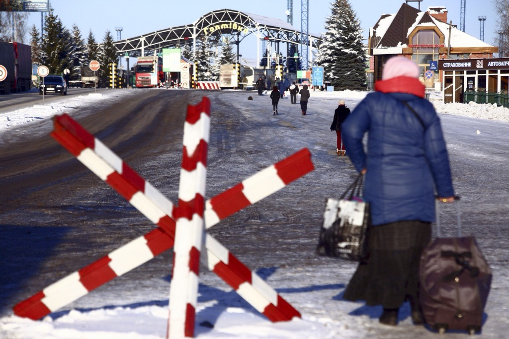 A woman walks to cross the checkpoint at the border with Russia in Hoptivka, Ukraine, Friday, Nov. 30, 2018. Ukrainian officials announced earlier on