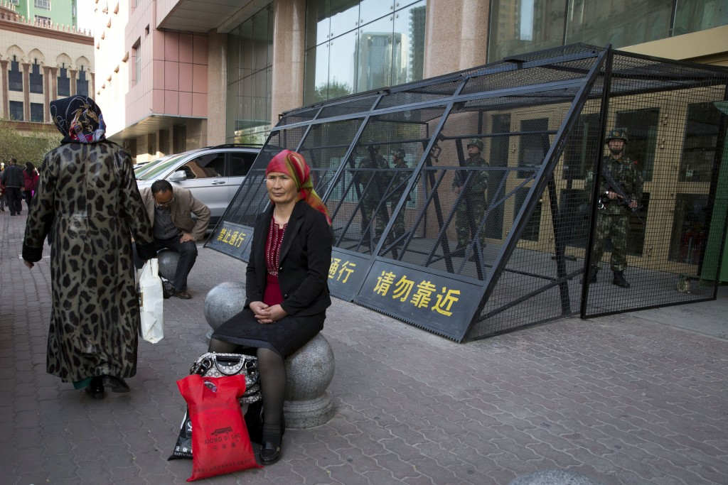 FILE - In this May 1, 2014, file photo, an Uighur woman rests near a cage protecting heavily armed Chinese paramilitary policemen on duty in Urumqi in