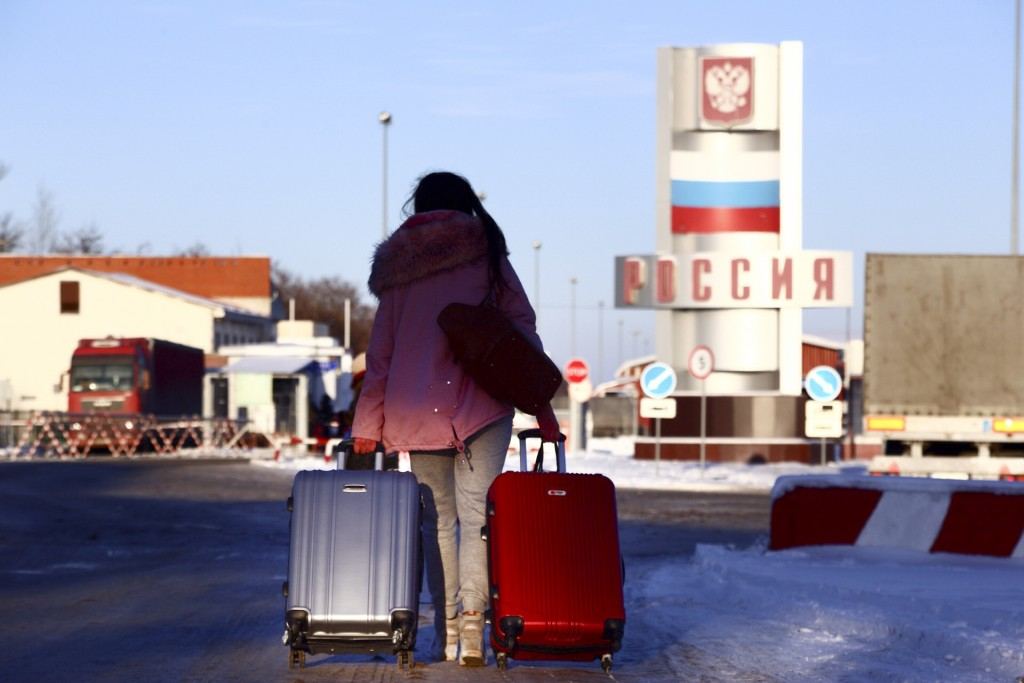 A woman prepares to cross the checkpoint at the border with Russia in Hoptivka, Ukraine, Friday, Nov. 30, 2018. Ukrainian officials announced earlier ...