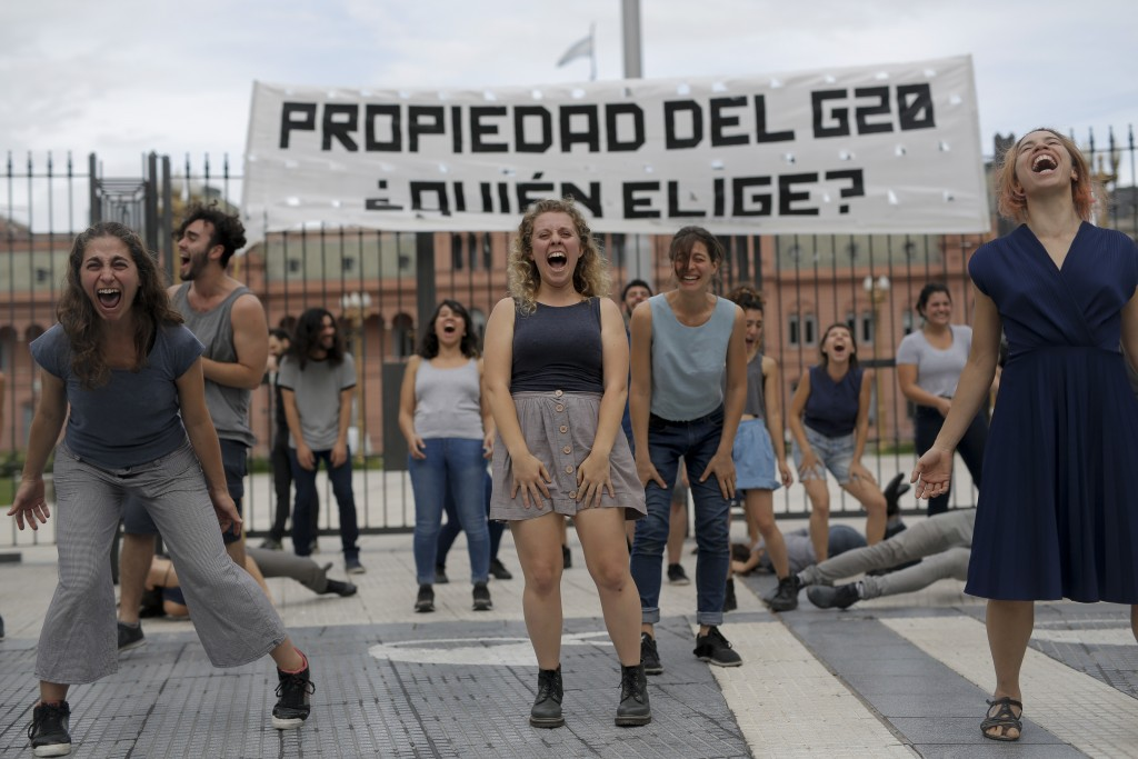 Actors stage a performance under a banner that reads in Spanish