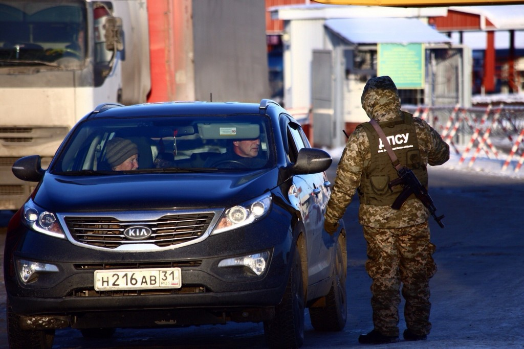 A Ukrainian border guard speaks to a driver of a car from Russia at the checkpoint at the border with Russia in Hoptivka, Ukraine, Friday, Nov. 30, 20...