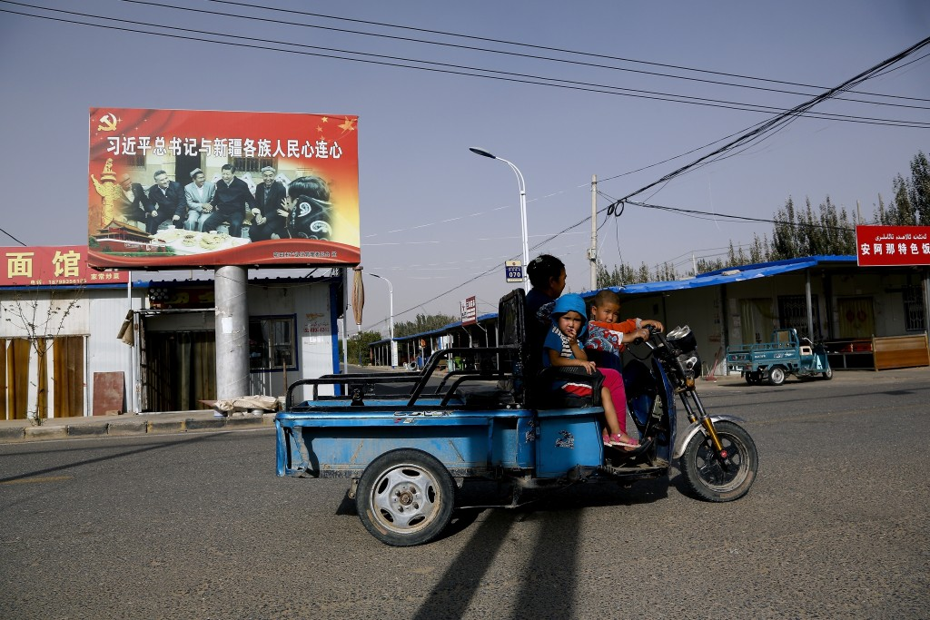 FILE - In this Sept. 20, 2018, file photo, an Uighur woman shuttles school children on an electric scooter as they ride past a propaganda poster showi
